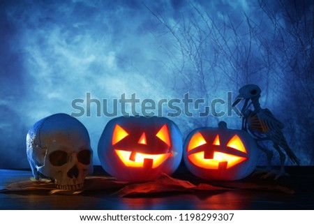 Halloween holiday concept. Pumpkins over wooden table at night scary, haunted and misty forest #1198299307