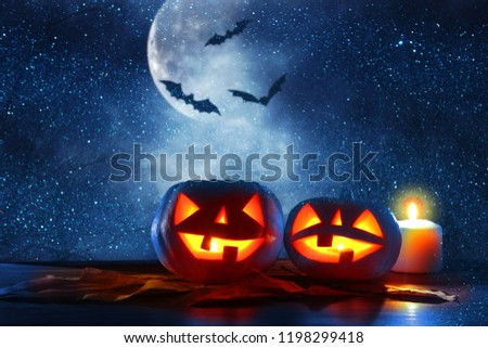 Halloween holiday concept. Pumpkins over wooden table at night scary, haunted and misty forest #1198299418