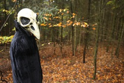 Halloween holiday concept. Skull crow costume. Scary bird in the autumn forest.Horror and fear concept. man in  bird skull mask and black cloak. Autumn holidays time. halloween mood