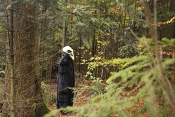 Halloween holiday concept. Skull crow costume. Scary bird in the autumn forest.Horror and fear concept. man in white bird skull mask and black cloak. Autumn holidays time. halloween mood