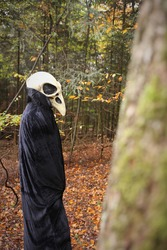Halloween holiday concept. Skull crow costume. Scary bird in the autumn forest.Horror and fear. man in white bird skull mask and black cloak. Autumn holidays time. halloween mood