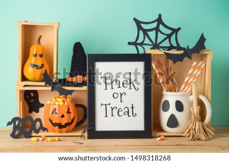 Halloween holiday concept with photo frame, jack o lantern cup, candy corn and decorations on wooden table