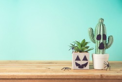 Halloween holiday creative concept with cactus plant jack o lantern character on wooden table