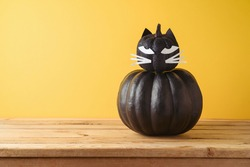 Halloween holiday creative concept with cute funny black pumpkin decor as black cat on wooden table over yellow background