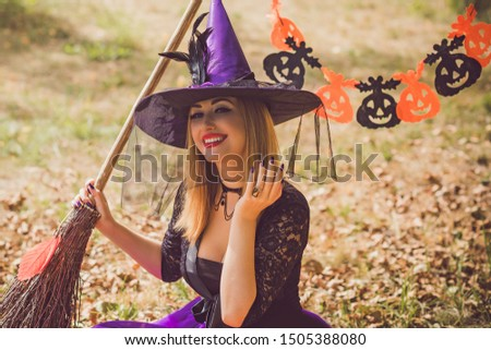 Halloween holiday witch Lady wear purple hat and stylish costume in Mystical atmosphere outdoors, celebrate autumn