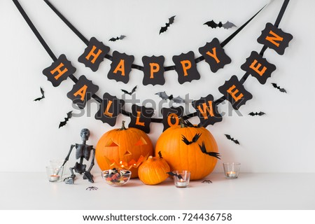 halloween, holidays and decoration concept - jack-o-lantern or carved pumpkins with candies and festive garland on white background