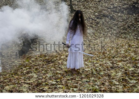 Stock Photo Halloween horror composition. Scaring dark haired girl in white dress with sword in the smoke and fog walking in the forest. Gothic darkness, ghost in the fog.