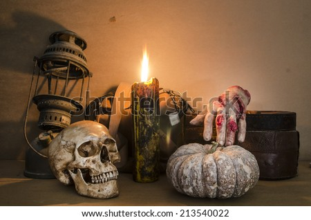 Halloween image with a burning candle on an ancient skull