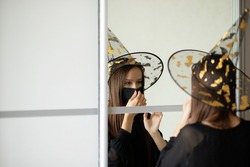 Halloween in coronavirus,girl in a protective medical mask costume in front of a mirror,safety and health care at parties on the eve of all saints