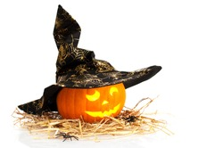 Halloween jack o lantern carved pumpkin wearing witches hat on straw with spiders and white background