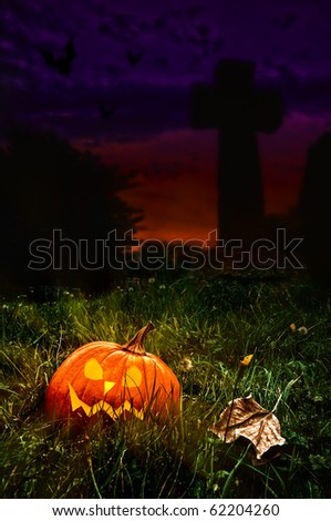 Halloween jack o lantern in cemetery with cross in background