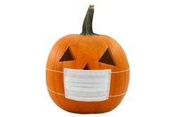 Halloween jack o'lantern jackolantern face pumplin wearing a covered pandemic covid-19 medical surgery mask carved
