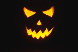 Halloween Jack-o-lantern on a black background, pumpkin with glowing in the dark eyes, the horror on Halloween