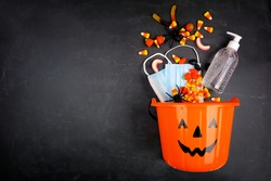 Halloween Jack o Lantern pail with spilling candy and COVID 19 prevention supplies. Top view over a black background.