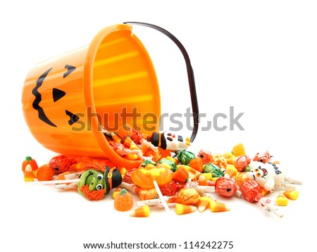 Halloween jack-o-lantern pail with spilling candy over white