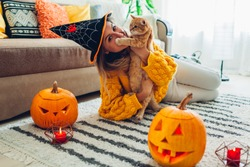 Halloween jack-o-lantern pumpkins. Woman in hat playing with cat lying on carpet decorated with pumpkins and candles.