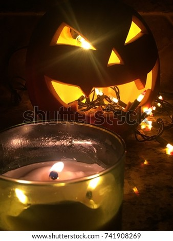 Halloween jack o lantern throwing up orange Halloween lights night illuminated scary spooky scene with pumpkin Stacey triangle eyes and cool lighting for American holiday shining lights in the camera  #741908269