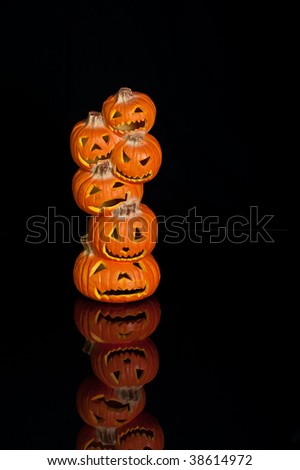 Halloween Jack O Lanterns already carved and sitting on a table.  One large stack of 6 small pumpkins on black with a reflection.