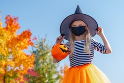 Halloween kids mask. Portrait blonde girl in witch costume with pumpkin bucket. Child wearing black face masks outdoors protecting from COVID-19.
