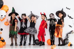 Halloween kids party concept, happy group of Asian cute little girls action modeling fashion in Halloween costume witch, skeleton, and face paint holding carving pumpkin in studio white background