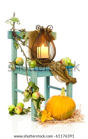 Halloween lantern on rustic chair decorated with apples and pumpkin