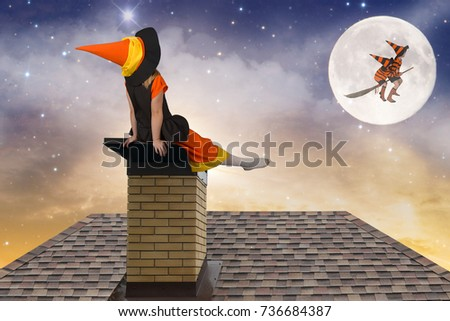 Halloween.Little girl in a witch costume sitting on the roof and look at the flight of witches and wizards in the sky. #736684387
