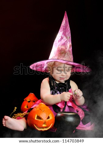 Halloween little girl witch with a carved pumpkin over black background with smoke