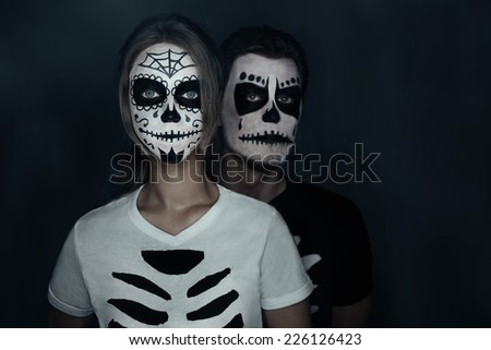 halloween loving couple in costumes of skeletons and sugar skull makeup