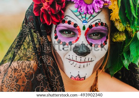 Stock Photo halloween make up sugar skull beautiful model with perfect hairstyle. Santa Muerte concept. Fashion retro toning. walks in the Park - the field