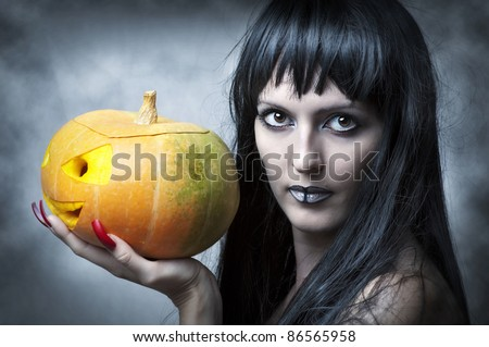 Halloween makeup. Sexy woman - Witch with long black hair and pumpkin smiling and look to shot