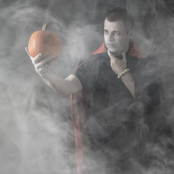 Halloween male vampire portrait. Caucasian white man holding orange pumpkin dressed and stylised for a nosferatu on dark smoky or misty background