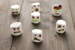 Halloween marshmallow zombies on a wooden background