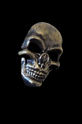 Halloween mask. Hypertrophied facial features, large brow ridges and cheekbones, empty black edges, eerie nasal bone. Unpleasant grin of teeth. Gilded mask slanted to the side. Guizer mask. Trick or