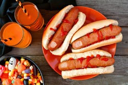 Halloween meal scene with hot dog fingers, drinks and candy, above view a wood background