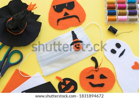 Halloween medical mask hand made DIY idea for decoration, symbols traditional for hand craft felt paper: pumpkin, ghost, spooky, witch hat in black, orange and white on yellow background Сток-фото ©