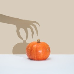 Halloween minimal concept with pumpkin and witch or zombie hand shadow. Creative spooky holiday fun background