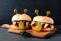 Halloween monster hamburgers on a paddle board against a black background