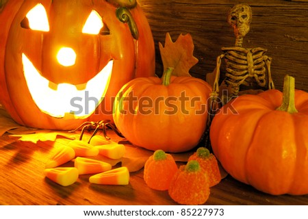 Halloween night scene closeup with glowing jack-o-lantern, pumpkins, candy and skeleton