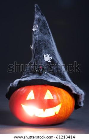 halloween orange pumpkin with witch hat over dark background