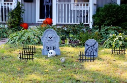 Halloween outdoor decoration background.Front yard of private house decorated by fake skull,bones hands,tombstones and grates,pumpkins on the porch for old american trick-or-treat Halloween tradition.