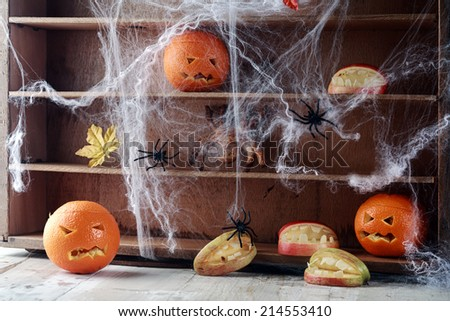 Halloween pantry with spider web covered shelves crawling with large black spiders and orange jack-o-lanterns with scary faces and a bat flying overhead