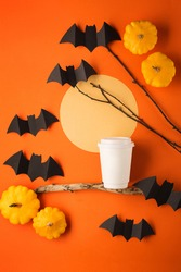 Halloween paper decorations on orange background and cup of coffee to go. Black bats, pumpkins, tree branch and moon. Halloween concept. Flat lay, top view, overhead. Party greeting card mockup.