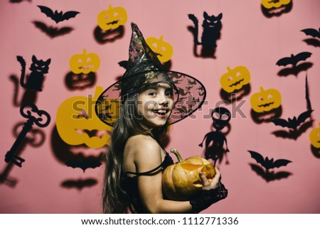 Halloween party and decorations concept. Girl with happy face on pink background with bats and pumpkins decor. Kid in spooky witches costume holds carved pumpkin. Little witch wearing black hat #1112771336