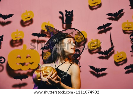 Halloween party and decorations concept. Kid in spooky witches costume holds carved pumpkin. Girl with romantic face on pink background with bats and pumpkins decor. Little witch wearing black hat. #1111074902