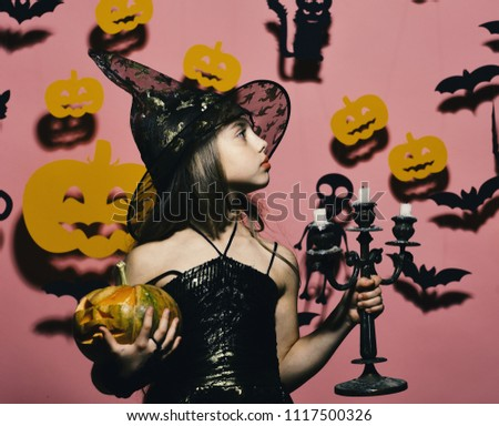 Halloween party and decorations concept. Kid in witches costume holds pumpkin and chandelier. Girl with proud face on pink background with bats and pumpkins decor. Little witch wearing black hat. #1117500326