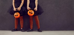 Halloween party banner. Cropped image of legs of two little girls with pumpkin candy bucket standing on black background. Children in black dresses and black and orange leggings stand near copy space