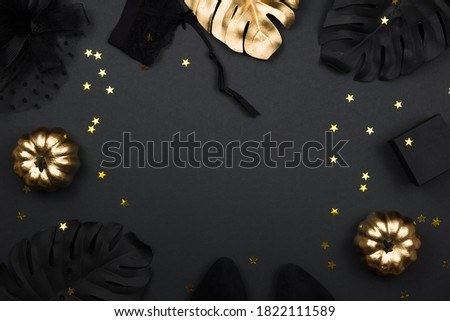 Photo of  Halloween party collection female outfit accessories on black background: hat with veil, garter belt, gifts. Black and gold pumpkins, flat lay, top view, copy space.