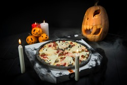 Halloween party decoration. Ghost pizza near spider web, pumpkin jack o lantern And black bats. Candle lights on smoke background. Fast food with cheesy silhouettes served on takeaway pizza box.