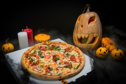 Halloween party decoration. Meat pizza near spider web, pumpkin jack o lantern And little spiders. Candle lights on smoke background. Fast food with champignons served on takeaway pizza box.