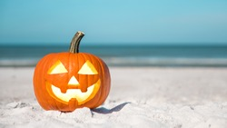 Halloween party on the beach. Pumpkin Jack-o'-lantern. Jack o lantern for Happy Halloween. Autumn season. On background ocean. Autumn in Florida. Fall season. Copy space.